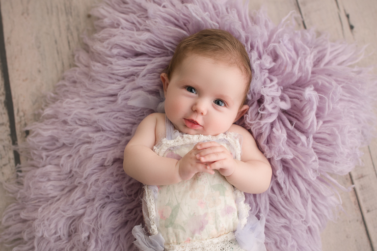 three month old baby girl on purple flokati in outfit