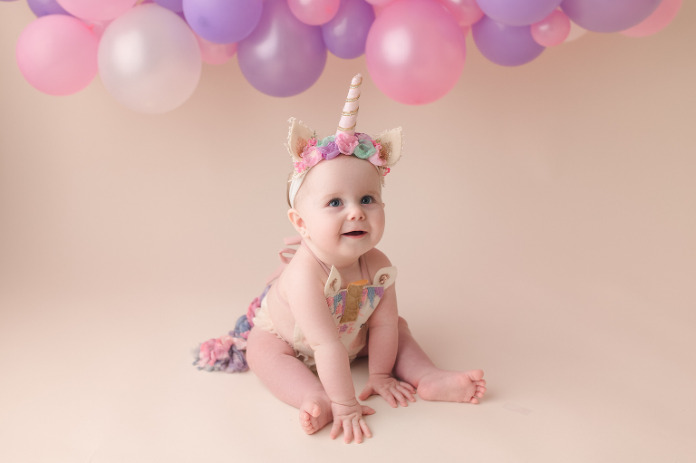 smiling one year old baby girl in unicorn outfit